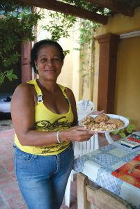 トリニダーのカーサで筆者らがお世話になったマイタ。得意のエビ料理を持ってポーズ
