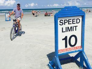 砂の上に走行車線があり、速度制限の標識が立っている。自転車もスイスイ