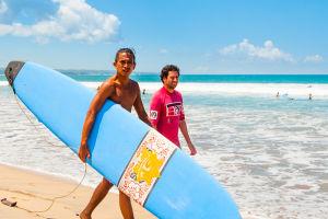 クタのビーチで、旅行者にサーフィンを教えるバリニーズの若者
