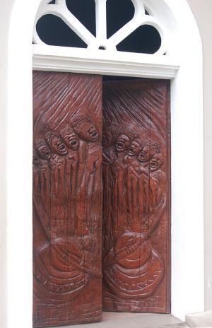 教会の扉の木彫り。セイシェルの歴史や文化、南国のイメージをモチーフにしている