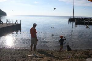 水辺で小石投げをして遊ぶ子供たち