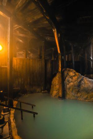 大きな岩と木の梁で作られた松楓荘の内風呂