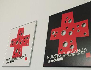 病院のシンボル、赤十字と銃弾の跡
