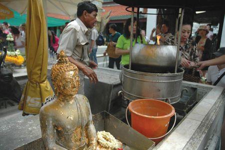 参拝者は、ロータスの花に浸した聖水を頭にかけて身を浄め、仏像に金箔を張って、祈りを捧げる