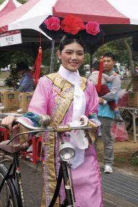 ひときわ目立つドレス姿で自転車を押す女性
