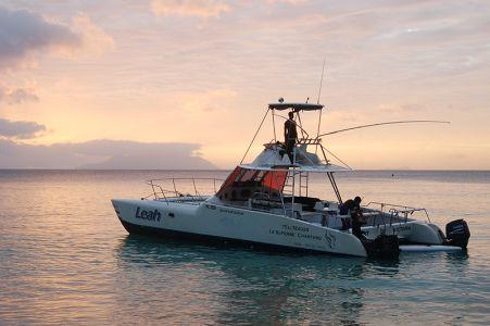 1日の仕事を終え、夕日の中、ボートを係留する青年たち