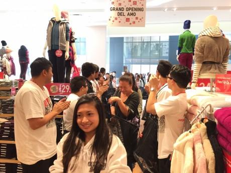 店員が拍手して迎える中、ユニクロの店舗で買い物する人たち
