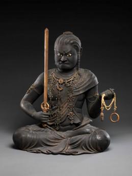 不動明王坐像 Kaikei, Japanese, active 1183–1223. Fudō Myōō. Japan, Kamakura period  (1185–1333), early 13th century. Lacquered Japanese cypress, color, gold, cut gold (kirikane), and inlaid crystal eyes. H. 21 in. (53.3 cm); H. to top of sword 21 1/2 in. (54.6 cm); W. 16 3/4 in. (42.5 cm); D. 15 in. (38.1 cm). Mary Griggs Burke Collection, Gift of the Mary and Jackson. Burke Foundation, 2015. Photo: courtesy of The Metropolitan Museum of Art.