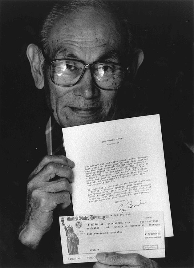 フレッド・コレマツ氏。1988年、長年の運動が実り、生存していた日系人収容者に2万ドルの補償金が配られた。その小切手を手にした写真 Photo by Shirley Nakao, Courtesy of the Korematsu Institute