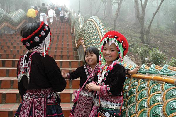 タイ北部の山岳少数民族の子供たち。伝統衣装をまとい、観光客や参拝客のためにダンスや写真撮影に応じるPhoto © Mirei Sato