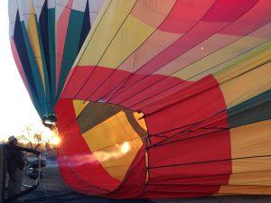 日の出とともに、炎をシュートしながら熱気球をふくらませるクルーPhoto © Mirei Sato
