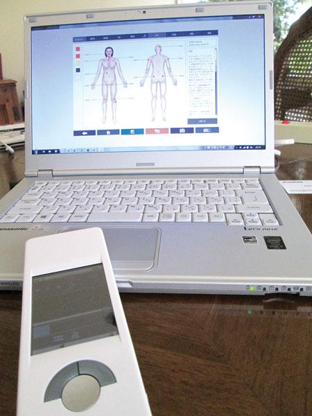 手前がmiHealthのデバイス、パソコン画面には診断結果が表示される